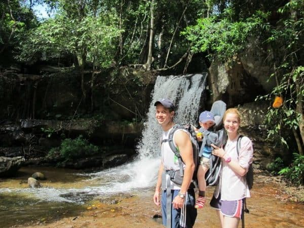 Two parents and a toddler hiking to a waterfall in siem reap