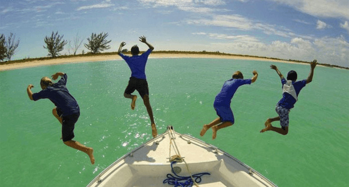 4 boys jumping off a boat in turks & caicos