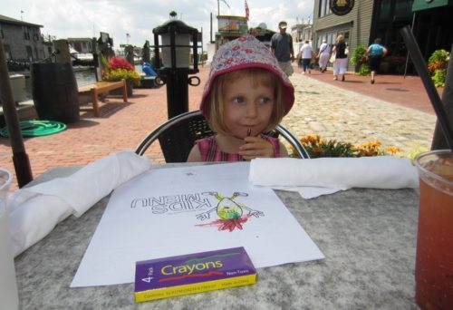 A preschooler sits at bowen's wharf restaurant with crayons and a kids menu.