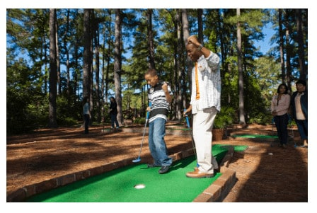 A father and son play putt-putt at the woodlands resort in virginia.