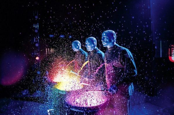 Blue man group has fun with paint, here they've poured it on lit up drums before banging away.