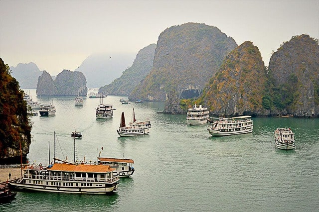 Halong bay provides a scenic break from vietnam's busy cities. Here, small tourist cruise boats dot the bay with caves behind.