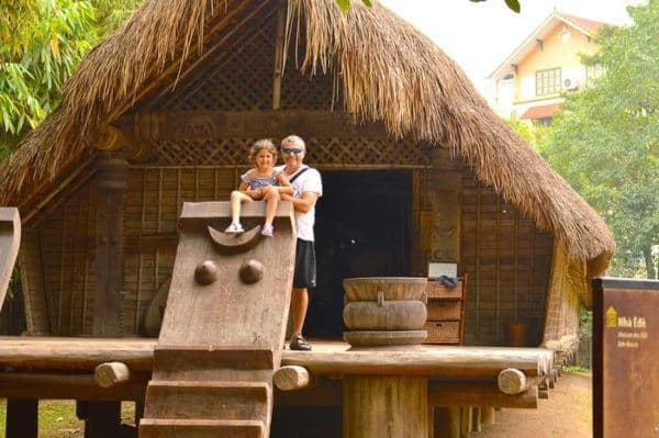 Kids love the traditional villages at the museum of ethnology in vietnam. A dad and daughter on the porch of a straw cottage.