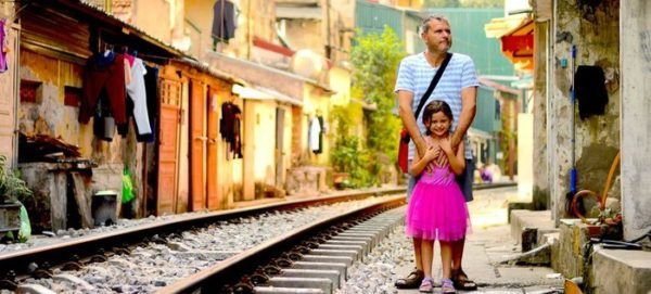 This railway village is a unique place in hanoi. A dad and daughter stand between the tracks a nd houses.