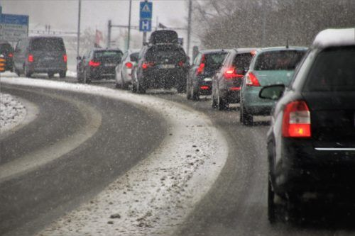 A long line of cars driving in snow.