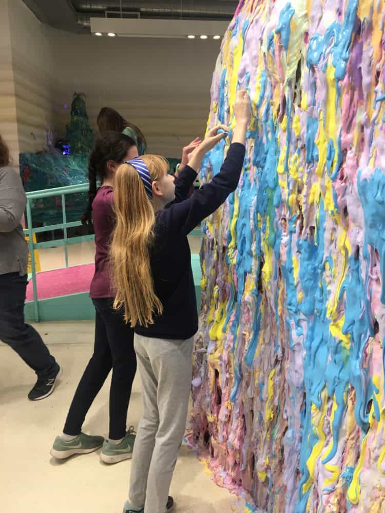 adding to the slime wall at the NYC Slime museum