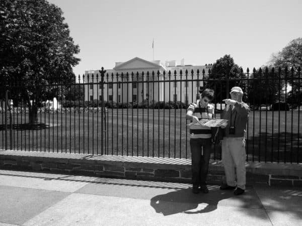 Tourists looking at a map outside the white house.