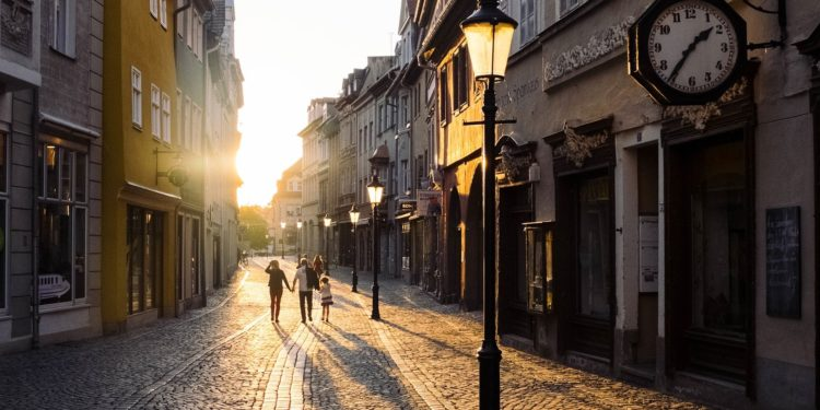 Family walking in a european city pedestrian zone at sunset