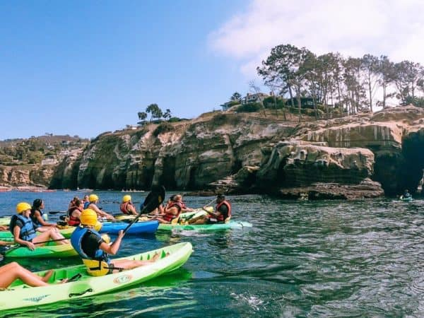 A group of kayaks pausing along the rocky coast off of la jolla, ca