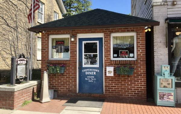 The front door of the tiny, red-brick cooperstown diner beckons with the promise of burgers and shakes.