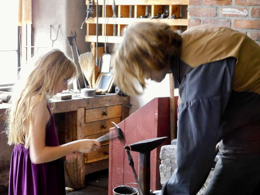 A blacksmith and a girl work on an iron project at the farmers' museum