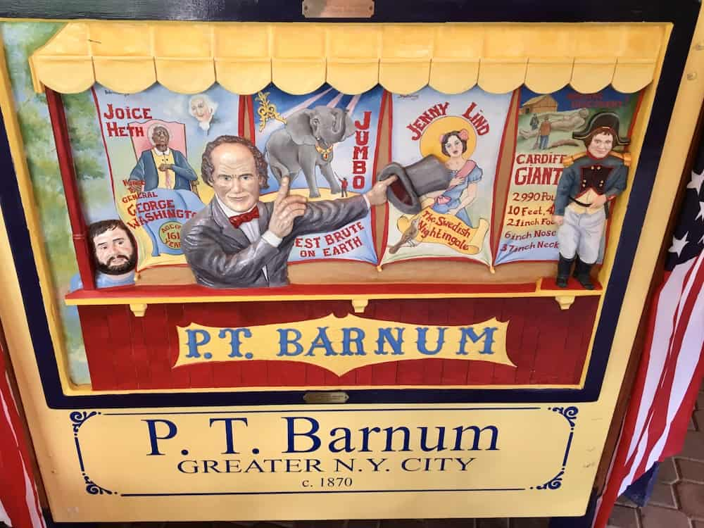 A tile on the empire state carousel celebrates new york native son p. T. Barnum promoting his circus.