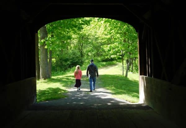 A girl and dad leaving the covered bridge on a nature trail in glimmerglass state park.