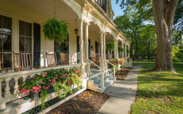 The long porch, rocking chairs and lawn a the family friendly inn at cooperstown.