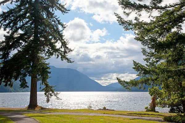 Lawn, pine trees, lake, mountains and sky. The view of crescent lake lodge in washington.