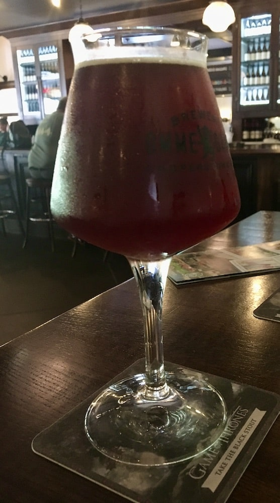 A stem-glass of dark fruit beer on a high-top table at the ommegang brewery.