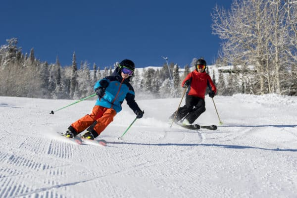 A father and a son skiing the wide beginner trails in park city, utah
